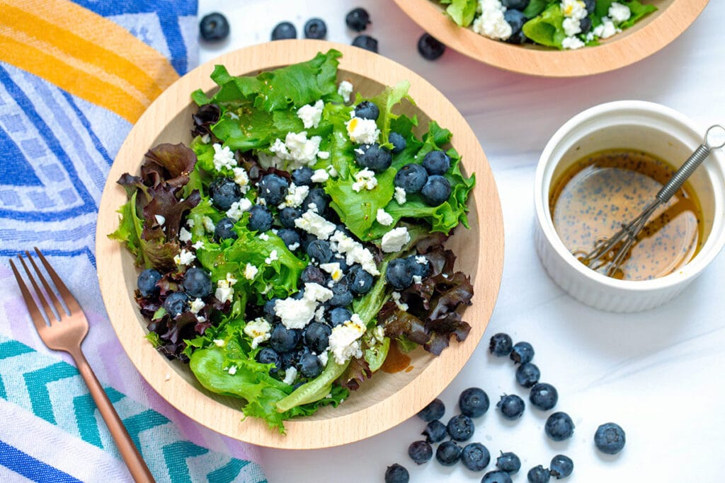 Landscape overhead view of blueberry feta salad with lettuce in bowl with small bowl of dressing and blueberries in background