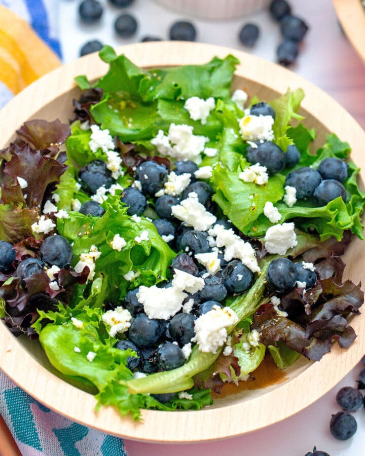 An overhead closeup view of a blueberry and feta salad with mixed greens and blueberries all around