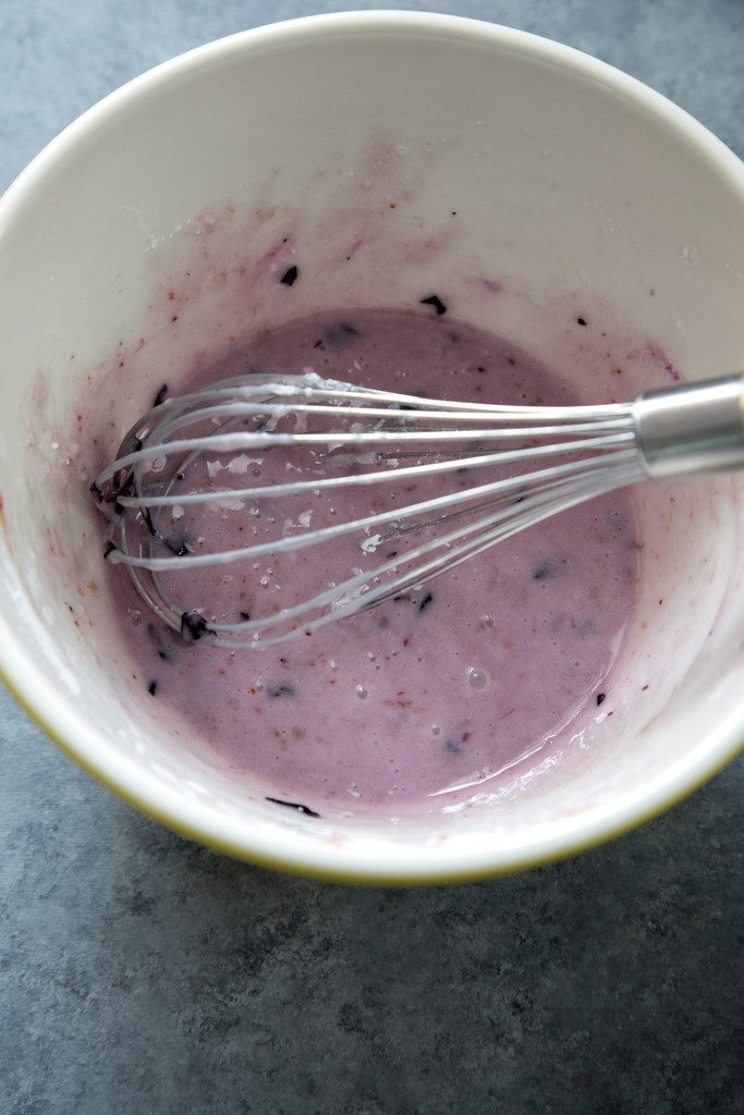 Overhead of a mixing bowl with blueberry icing and a whisk