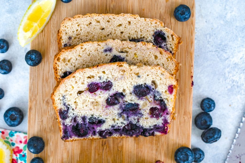 Landscape view of three slices of blueberry lemon bread on a cutting board with blueberries and lemon wedges around