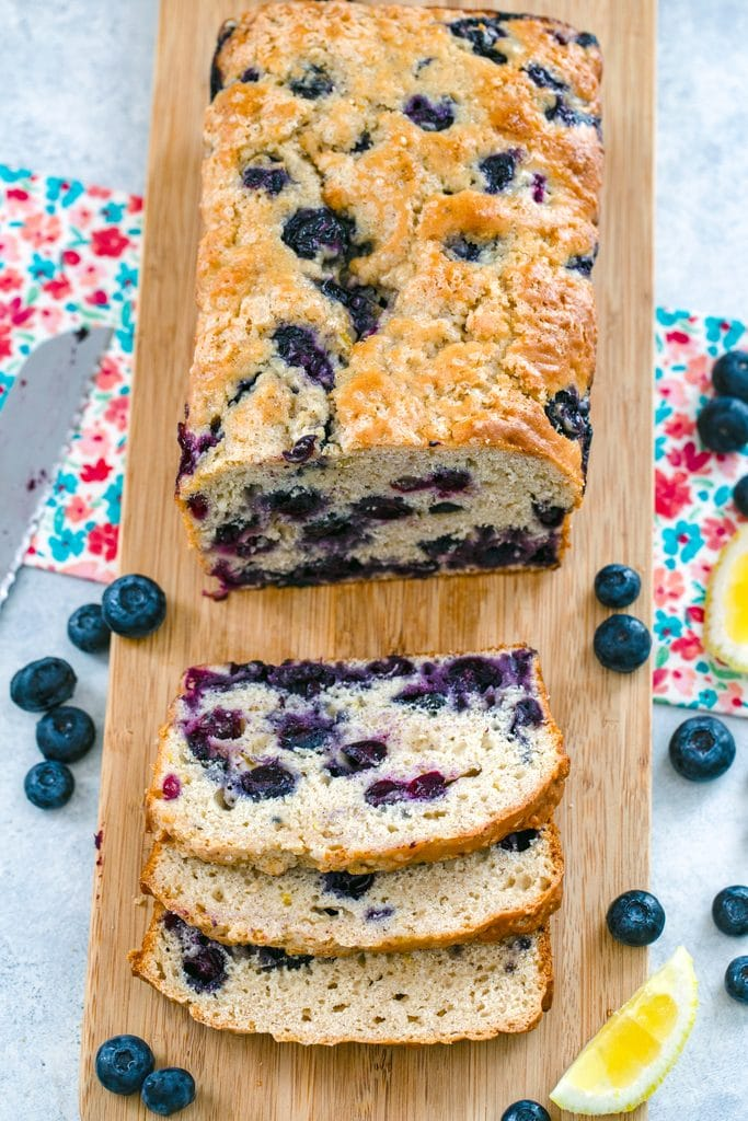 Overhead view of a loaf of blueberry lemon bread on a wooden cutting board with a few slices cut out and blueberries and lemon wedges around