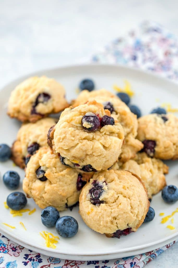 Up-close view of gray plate with stack of blueberry, lemon, and white chocolate chunk cookies, surrounded by blueberries and lemon zest on a floral napkin