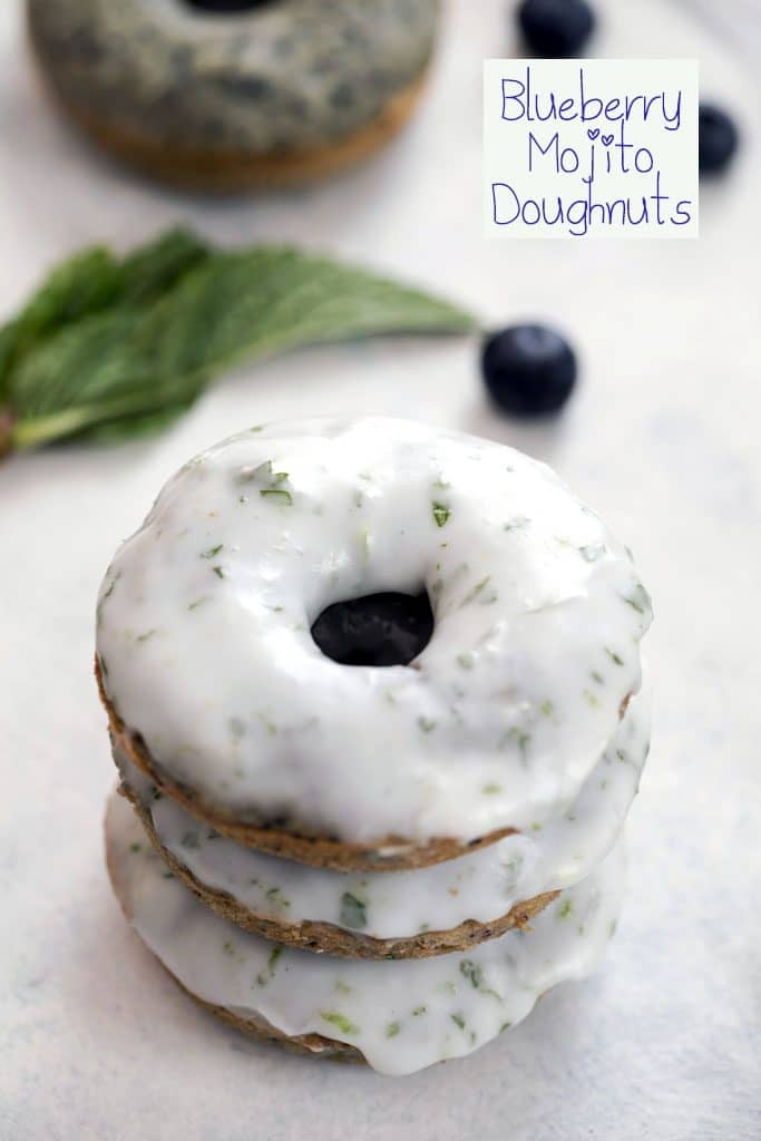 "Close-up of a stack of three blueberry mojito doughnuts covered in icing with blueberries and mint in the background and ""Blueberry Mojito Doughnut"" text at the top"