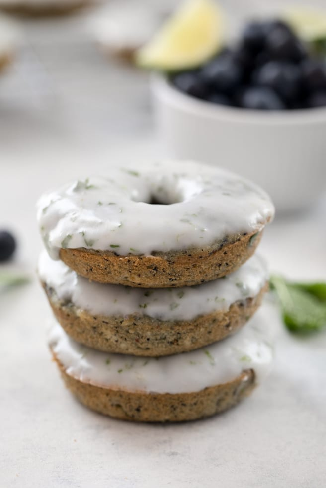 A close-up head-on view of a stack of three blueberry mojito doughnuts covered in mint lime icing with a bowl of blueberries and a lime wedge in the background