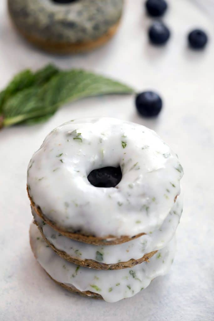 Close-up of a stack of three blueberry mojito doughnuts covered in icing with blueberries and mint in the background