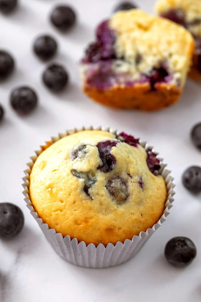 Overhead view of a blueberry muffin with pancake mix with muffin half in background and blueberries all around