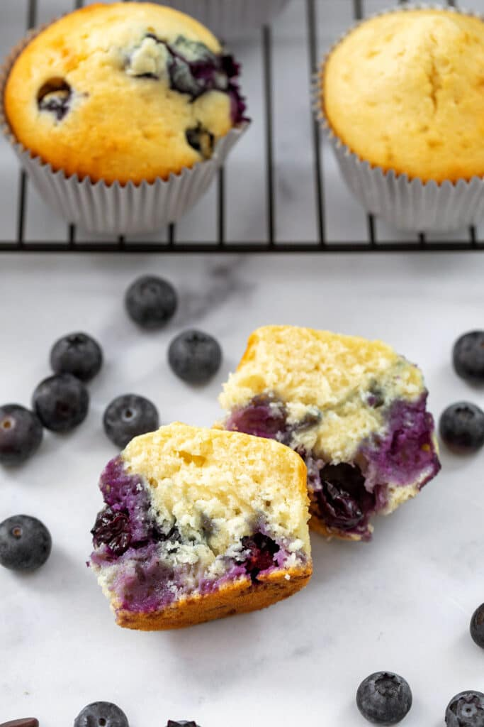 Blueberry Muffins made with pancake mix cut in half with more muffins behind it and blueberries all around