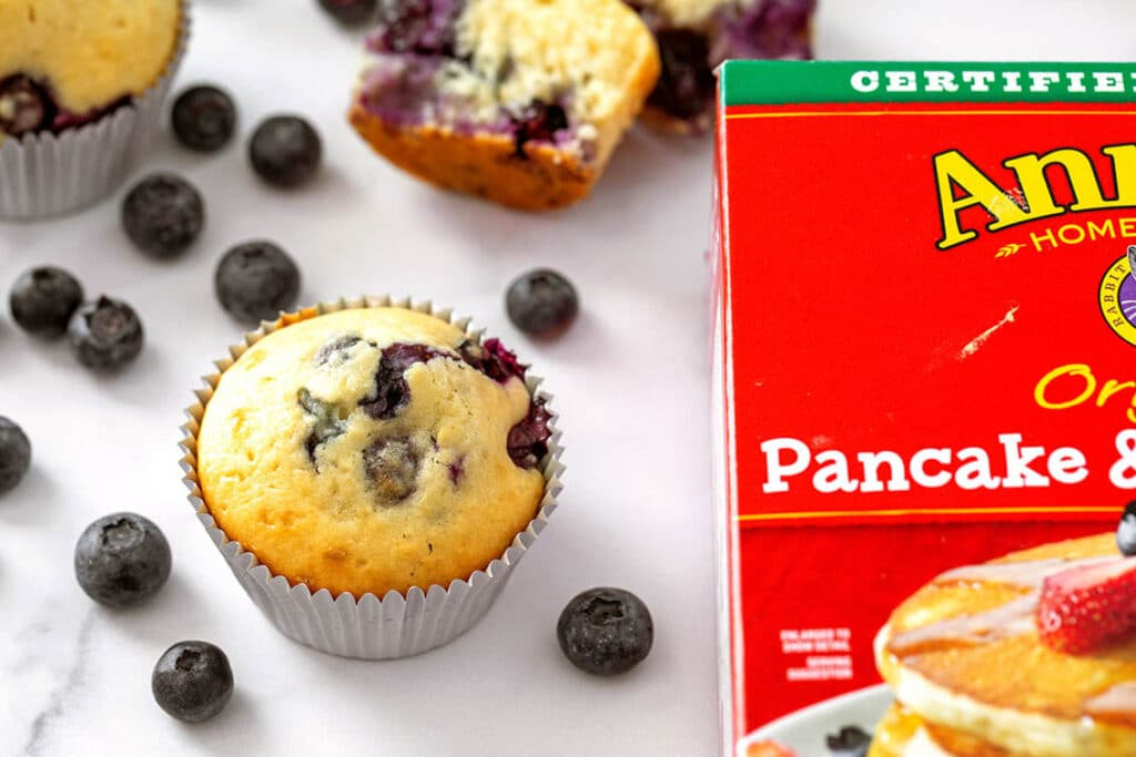 Overhead view of a blueberry muffin with blueberries all around and a red box of pancake mix to the side