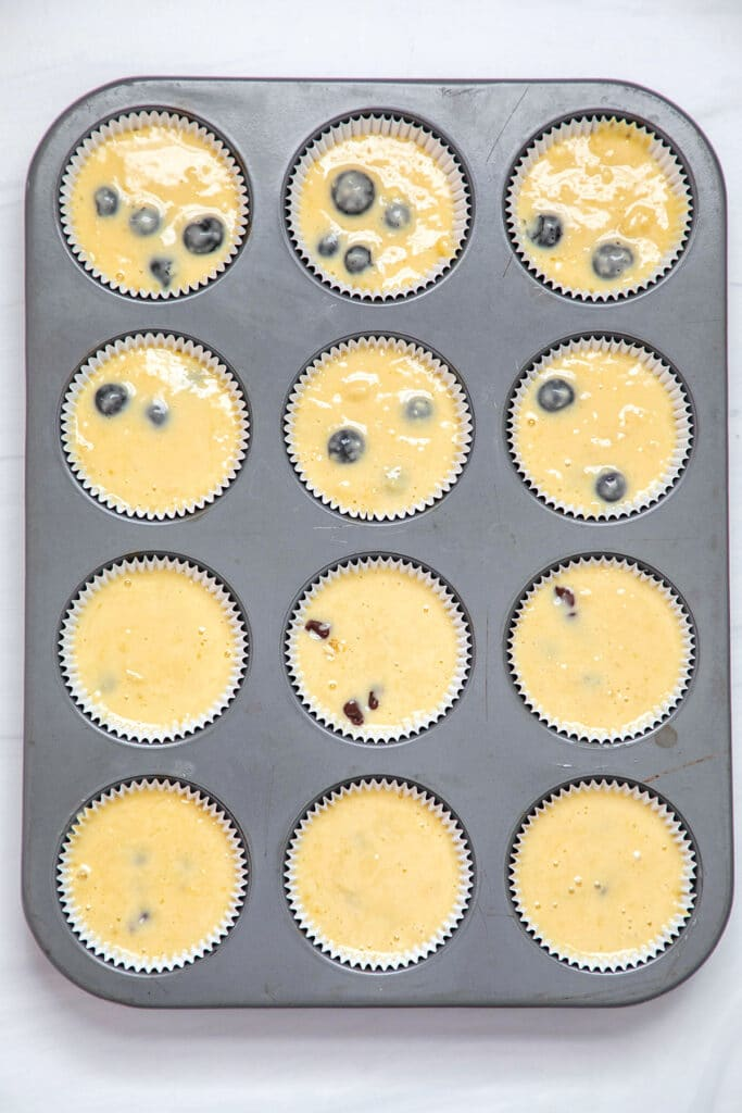 Overhead view of a muffin tin filled with batter ready for the oven
