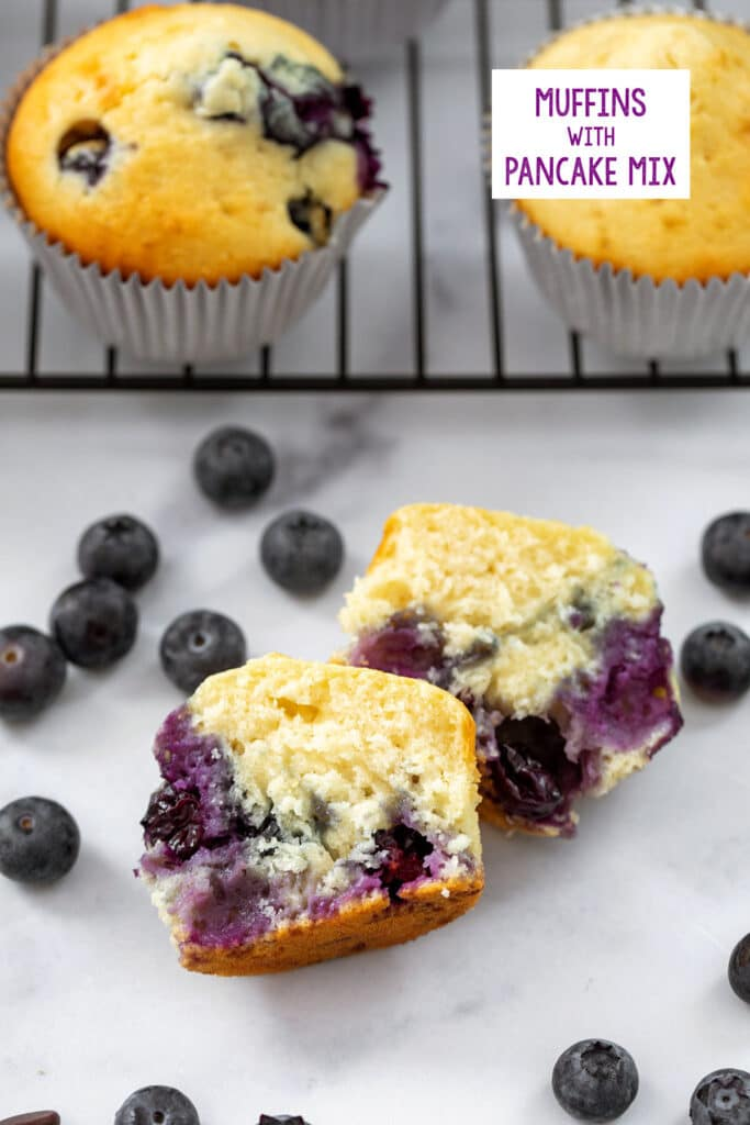 Blueberry Muffins made with pancake mix cut in half with more muffins behind it and blueberries all around and recipe title at top