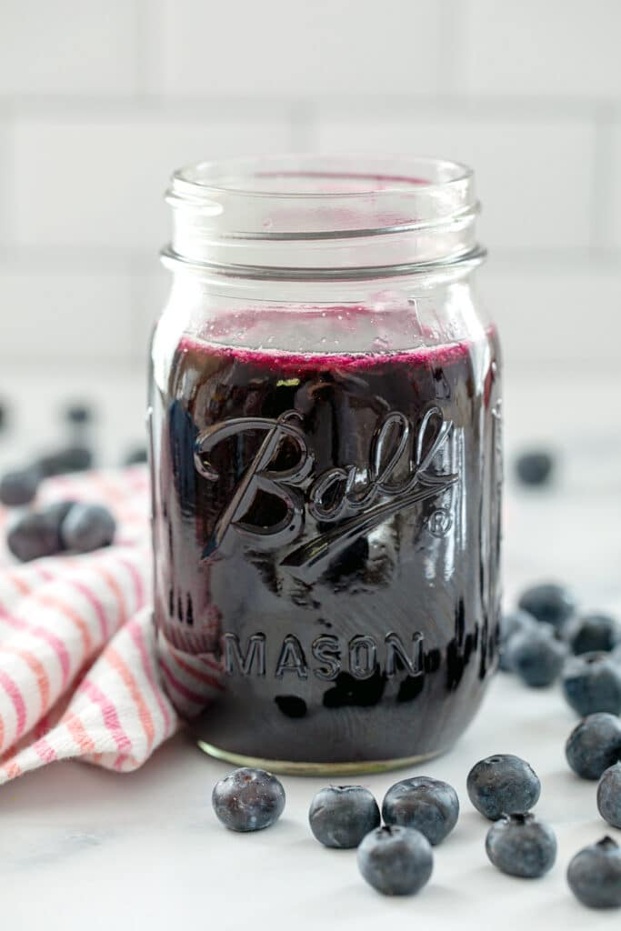 Head-on view of a mason jar of blueberry simple syrup with fresh blueberries all around