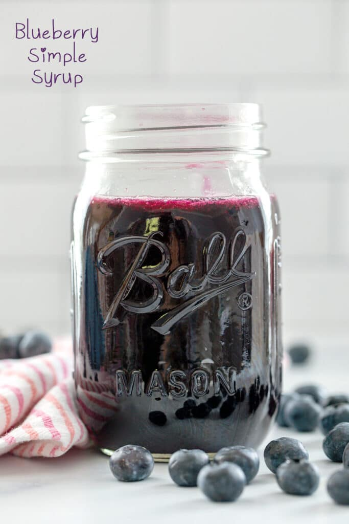 Head-on view of a jar of blueberry simple syrup with blueberries all around and recipe title at top