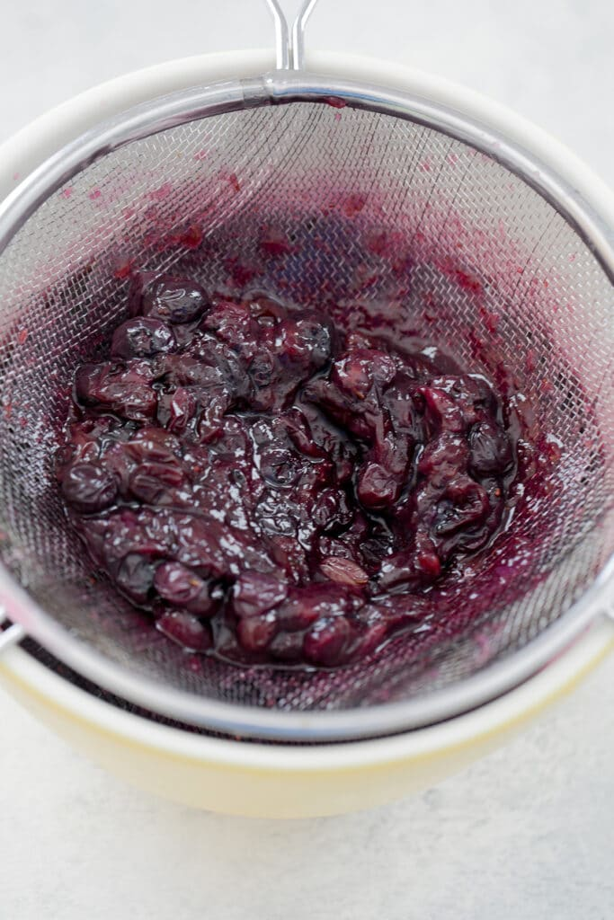 Blueberries being strained out of simple syrup over bowl