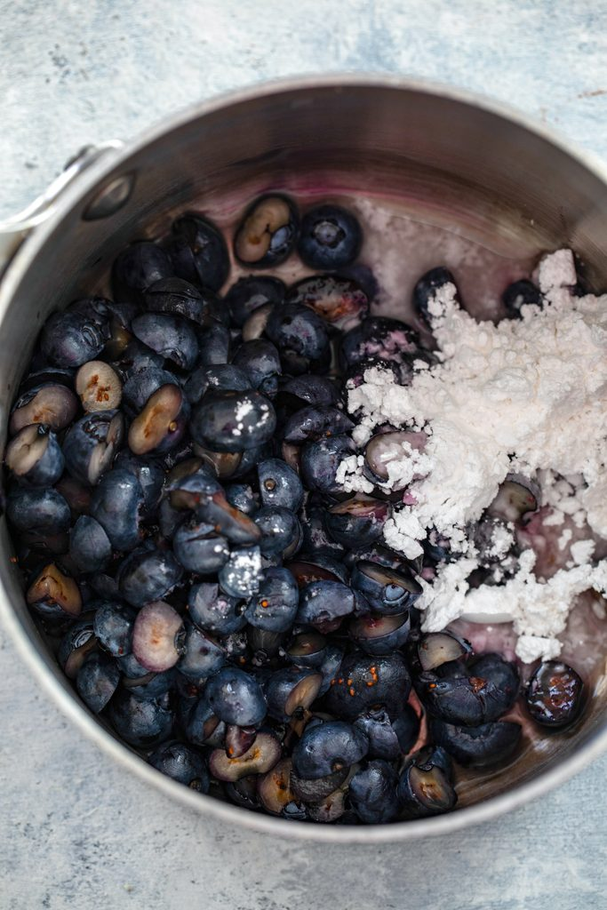Overhead view of blueberries, water, and confectioners' sugar in saucepan