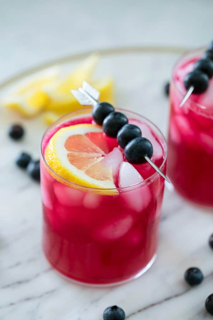 Glass of magenta colored blueberry vodka lemonade in a glass with eyes topped with a skewer of blueberries and a lemon wedge on a marble platter with blueberries and lemons in the background