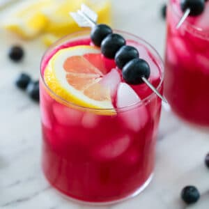 Overhead view of purple blueberry vodka lemonade with blueberry skewer and lemon wedge with second cocktail, blueberries and lemon wedges in background
