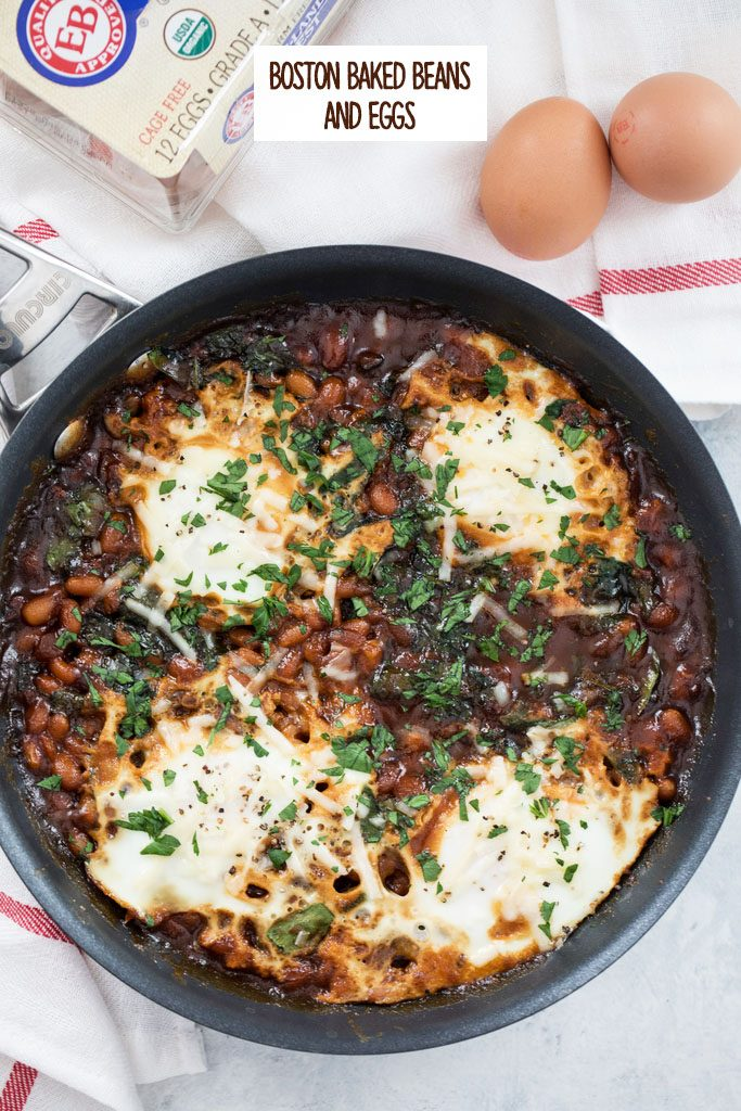 Overhead view of a skillet with Boston baked beans and eggs topped with parsley with whole eggs in the background and recipe title at top