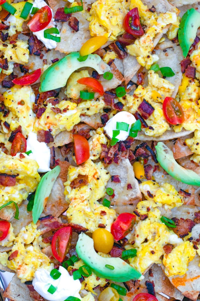 Overhead closeup of breakfast nachos including pita chips with bacon, scrambled eggs, avocado, tomato, and sour cream