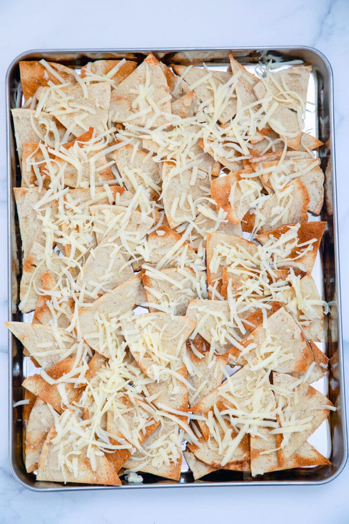 Homemade pita chips on sheet pan topped with shredded cheese