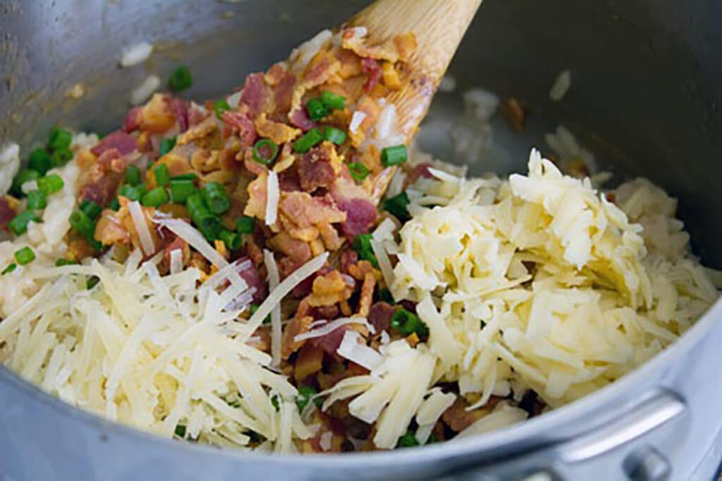 Rice in saucepan with crispy bacon, cheese, and scallions being stirred in
