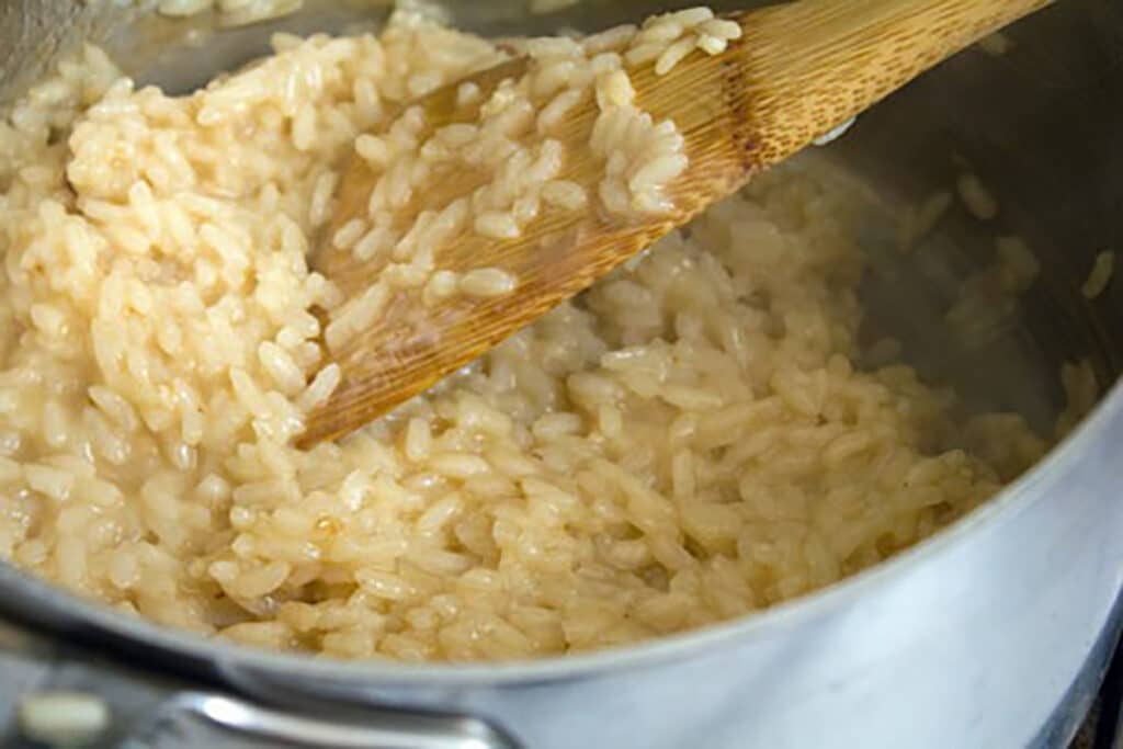 Arborio rice in saucepan with chicken broth added in