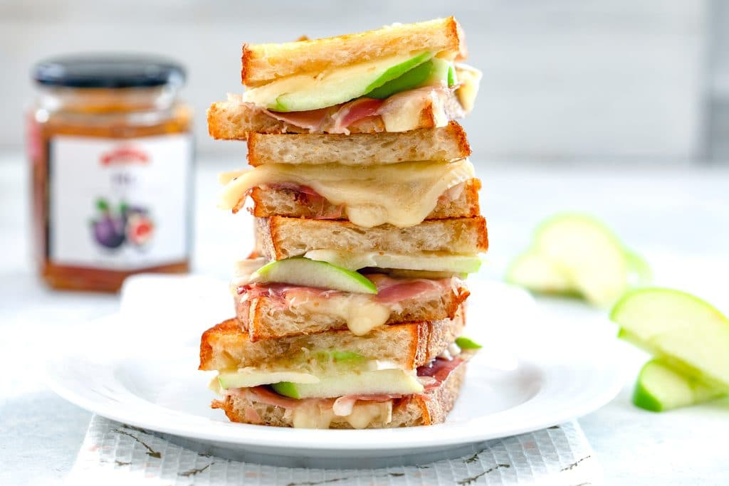 Landscape photo of four halves of a brie grilled cheese sandwich with green apple and prosciutto stacked on each other on a white plate with more apple and jar of fig spread in the background