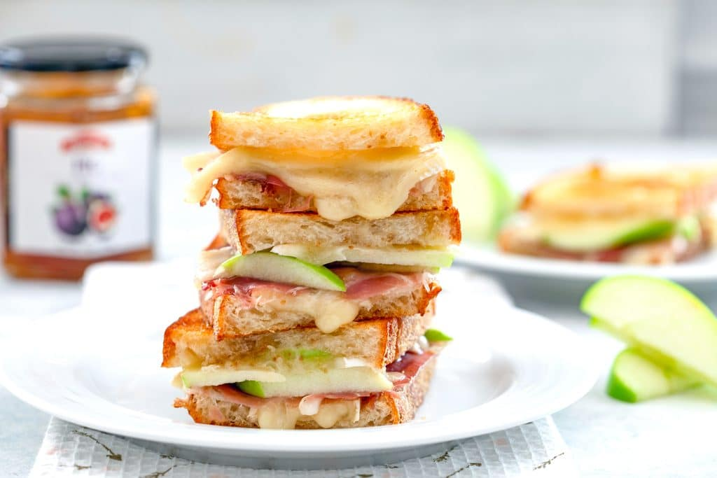 Landscape photo of three halves of a bri grilled cheese sandwich with green apples and prosciutto stacked on top of each other on a white plate with apples and jar of fig spread in the background