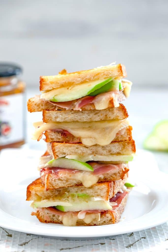 Four halves of a brie grilled cheese sandwich with fig spread, green apple, and prosciutto all stacked on each other on a white plate