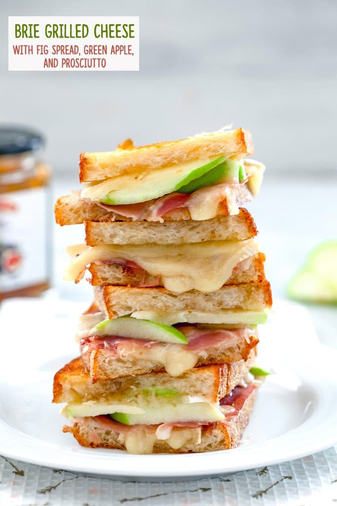 Four halves of a brie grilled cheese sandwich with fig spread, green apple, and prosciutto all stacked on each other on a white plate with recipe title at the top of the photo