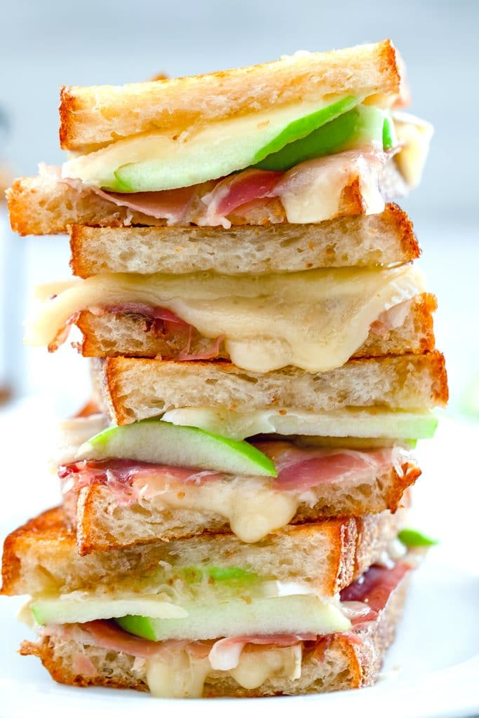 Close-up head-on photo of four halves of a brie grilled cheese sandwich with fig spread, green apple and prosciutto stacked on top of each other