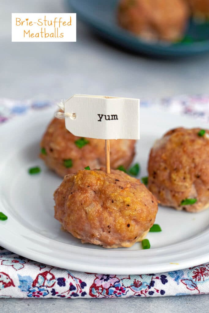 "Head-on closeup of a brie-stuffed meatball on a plate with a ""yum"" toothpick in it with two other meatballs in background and recipe title at top of image"