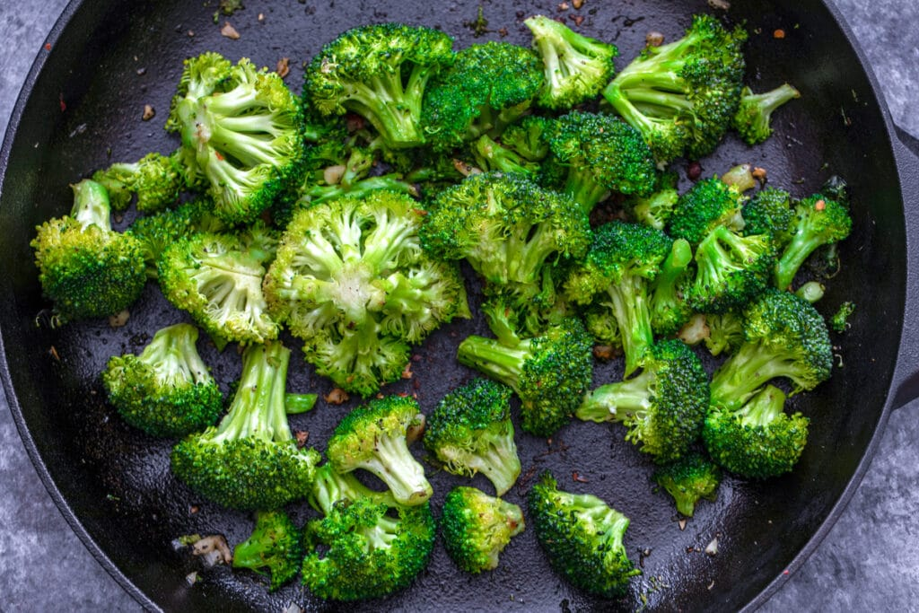 Overhead view of broccoli and garlic cooking in skillet