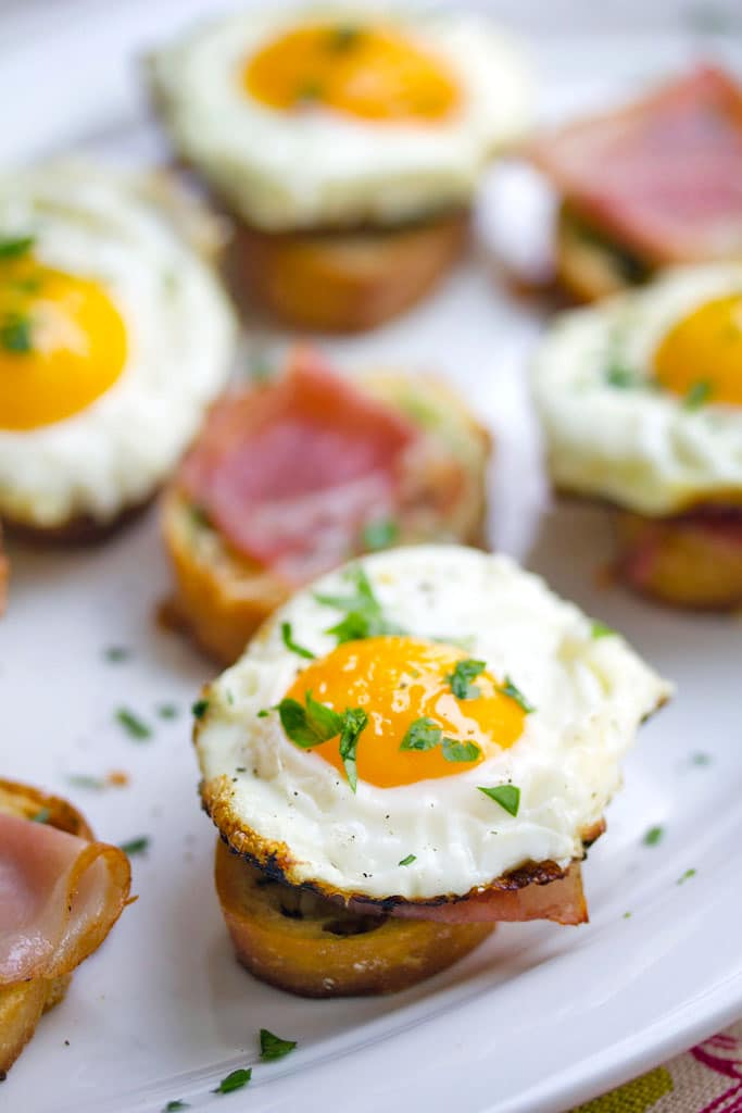 Overhead view of multiple brunch bruschetta with prosciutto and fried eggs with chopped parsley on a white platter