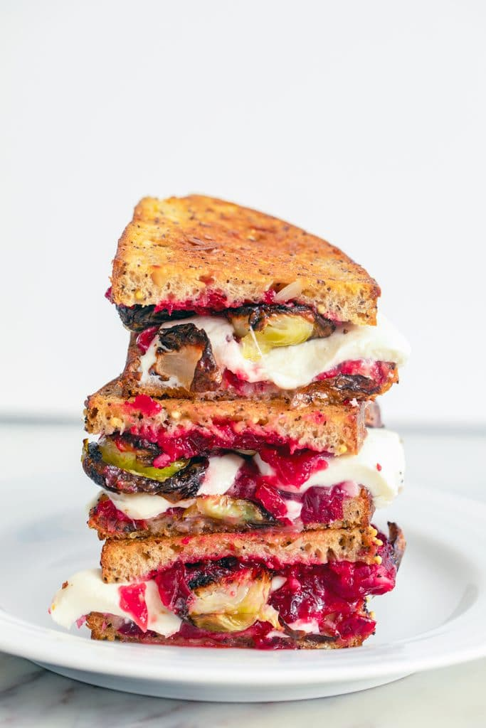 Head-on view of three brussels sprouts and cranberry relish grilled cheese stacked on each other on a white plate