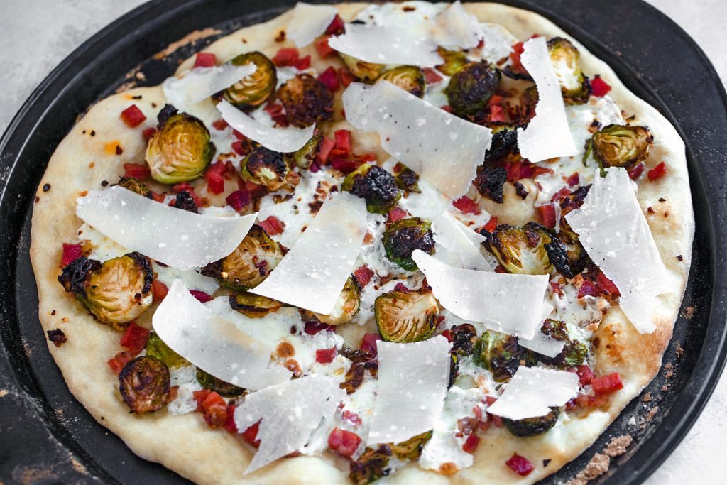 Landscape overhead view of brussels sprouts and pancetta flatbread just out of the oven and topped with shaved parmesan cheese