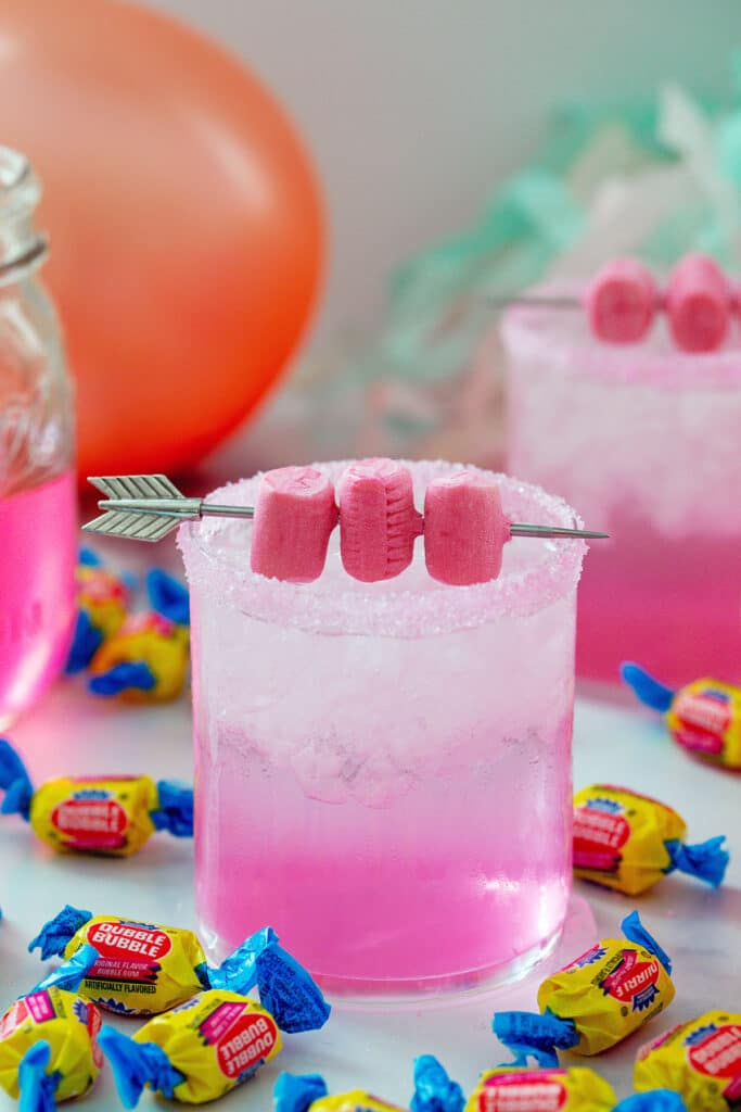 Head-on view of a pink bubblegum cocktail with gum garnish and Double Bubble gum all around with pink balloon and simple syrup in background