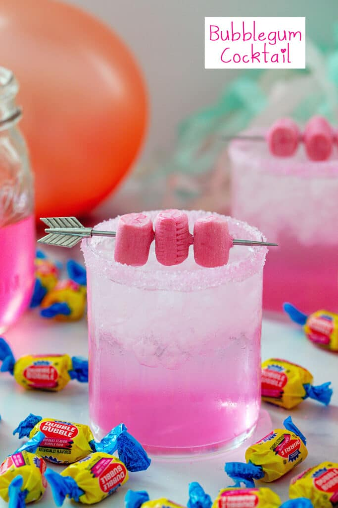 Head-on view of a pink bubblegum cocktail with gum garnish and Double Bubble gum all around with pink balloon and simple syrup in background and recipe title at top