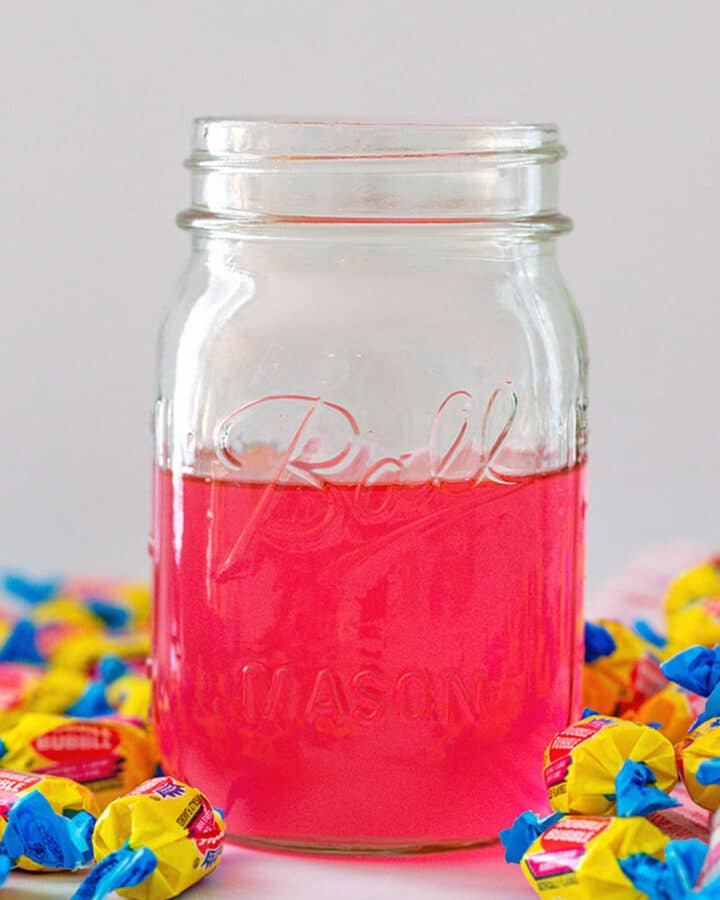 Head-on closeup view of a jar of pink bubblegum simple syrup with Double Bubble gum all around