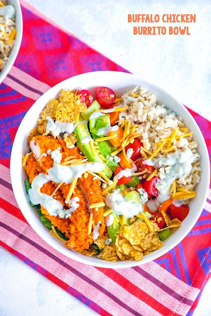 Overhead view of buffalo chicken burrito bowls with chicken avocado, tortilla chips, tomatoes, cheese, and rice, drizzled with blue cheese dressing and recipe title at top