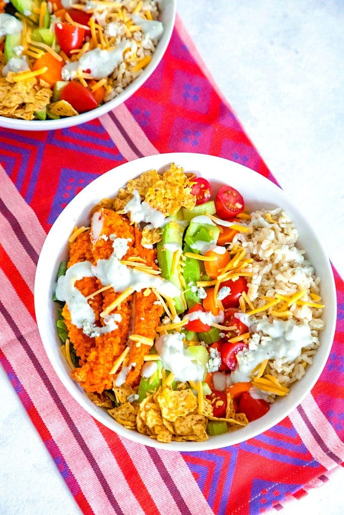Overhead view of buffalo chicken burrito bowls with chicken avocado, tortilla chips, tomatoes, cheese, and rice, drizzled with blue cheese dressing with second salad bowl in background