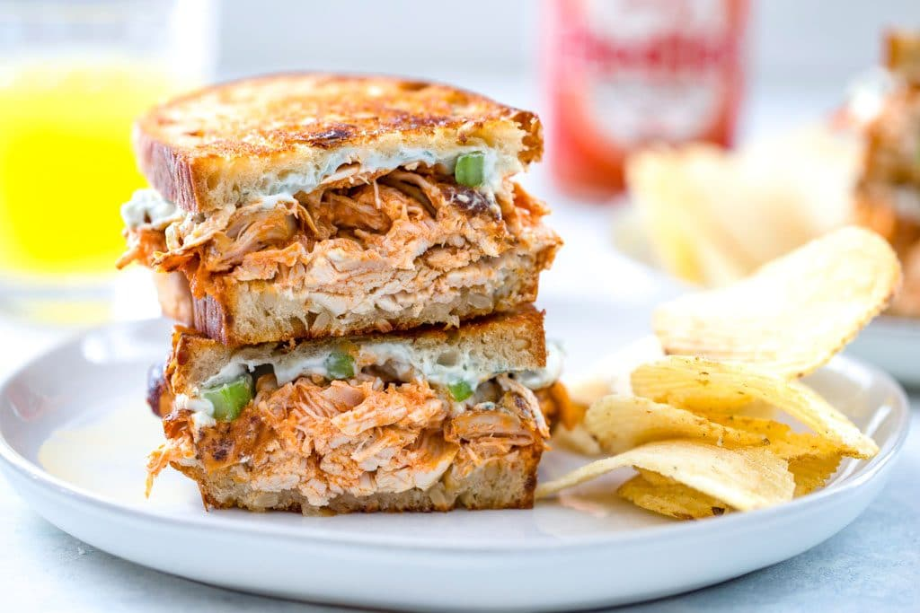Landscape photo of two halves of buffalo chicken grilled cheese stacked on each other on gray plate with potato chips on plate and juice and Frank's Red Hot bottle in background