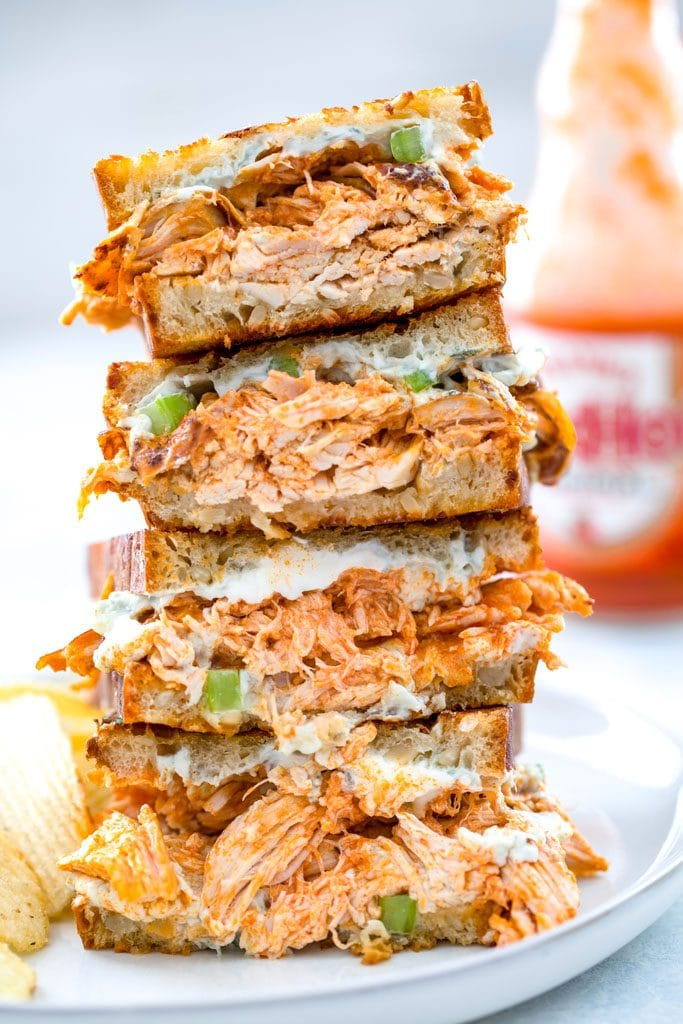 Four halves of buffalo chicken grilled cheese sandwich all stacked on each other on a gray plate with bottle of Frank's Red Hot in the background