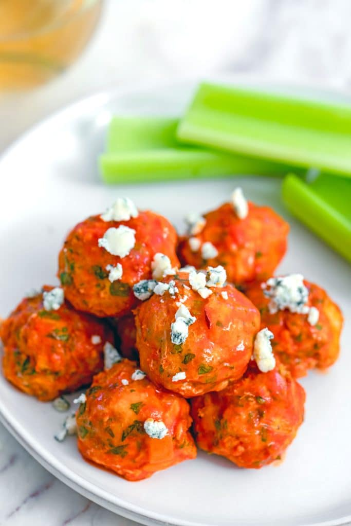 Overhead closeup view of buffalo chicken meatballs on plate with blue cheese and celery sticks