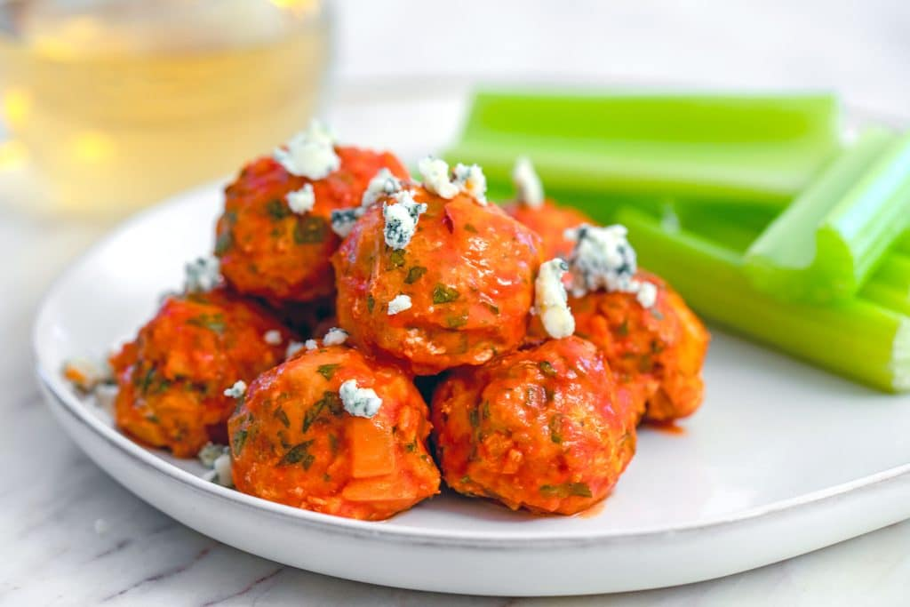 Landscape view of buffalo chicken meatballs on plate with blue cheese and celery sticks with glass of white wine in background
