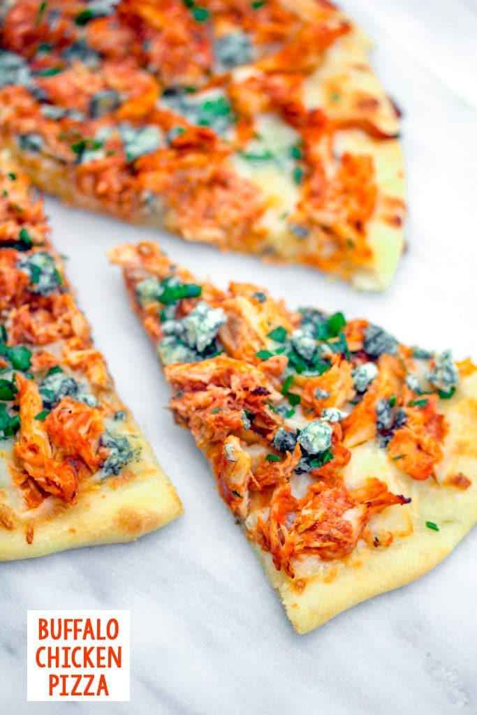 Overhead view of a slice of buffalo chicken pizza pulled out from the rest of the pizza on a marble surface with recipe title at bottom of photo