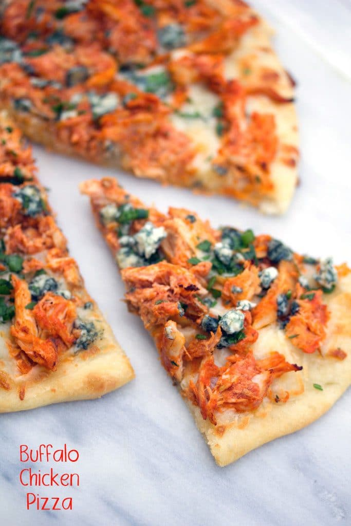 "A closeup of buffalo chicken pizza on a marble surface with a slice pulled out and topped with parsley, chives, and blue cheese with ""Buffalo Chicken Pizza"" text at top"