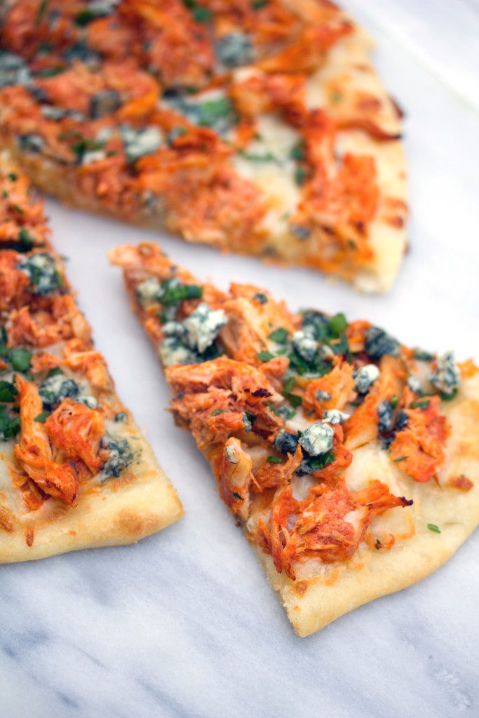 A closeup of buffalo chicken pizza on a marble surface with a slice pulled out and topped with parsley, chives, and blue cheese