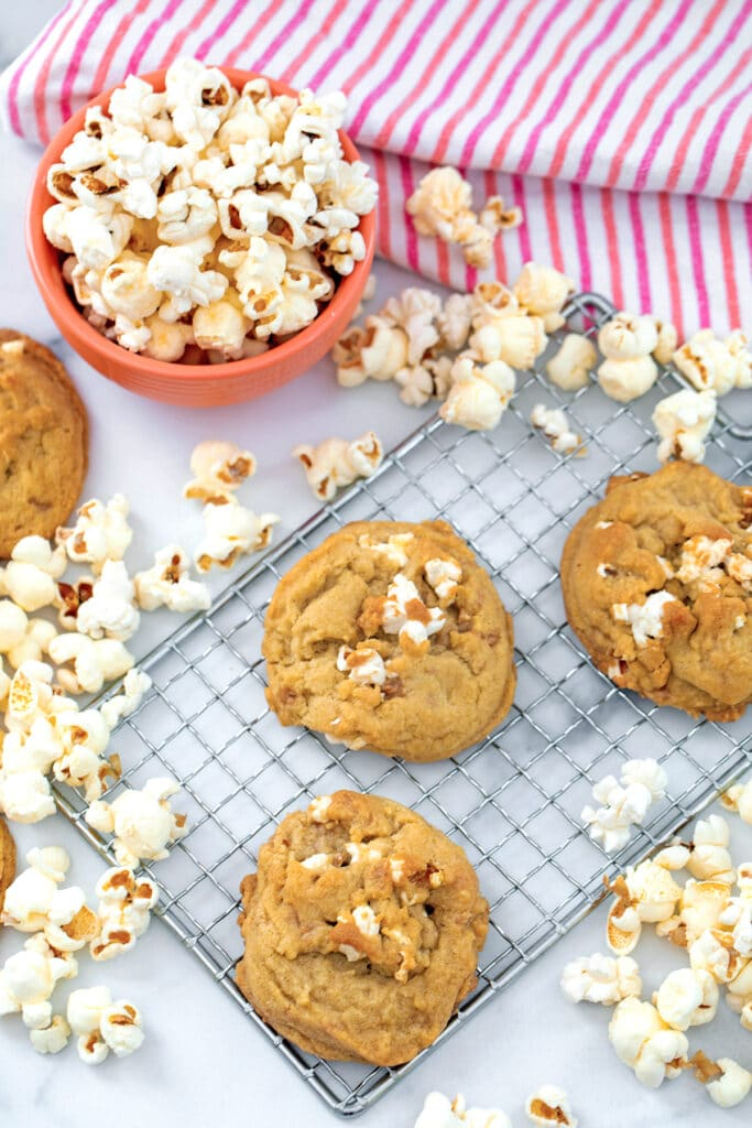 Buttered popcorn cookies on a metal rack with popcorn all around