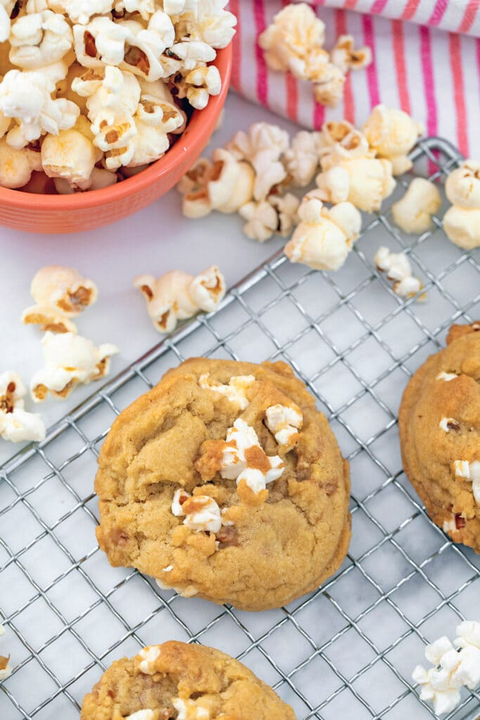 Overhead view of buttered popcorn cookies on metal rack with popcorn all around