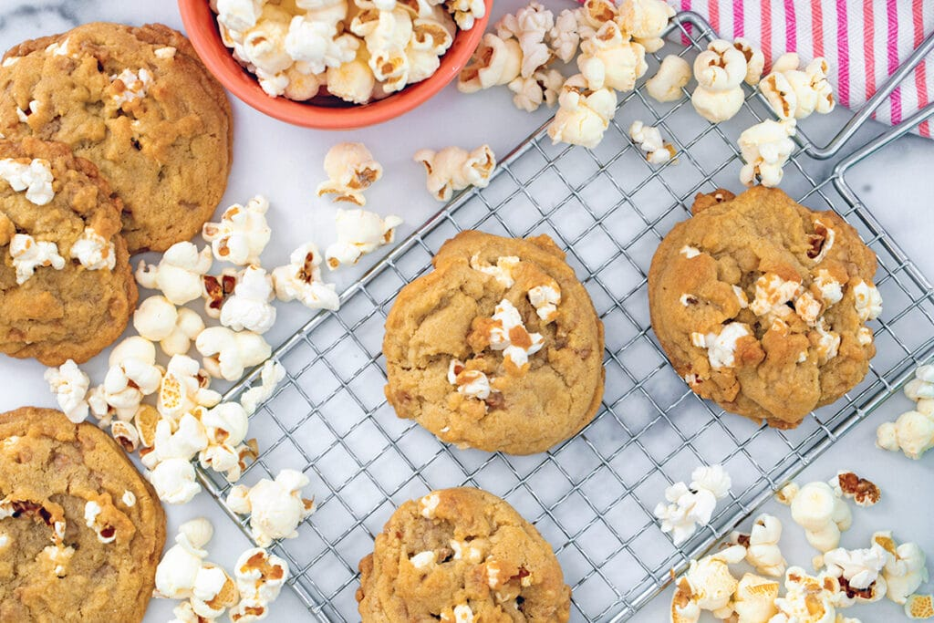 Landscape overhead view of buttered popcorn cookies on metal rack with popped popcorn and more cookies all around